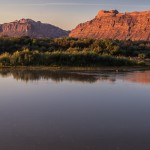 Panorama of the sunrise reflecting on the red rocks in Moab reflecting onto the Colorado River